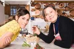 Italian mother and daughter in kitchen - stock photo