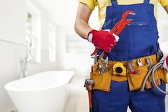 plumber with tool belt standing in bathroom - stock photo