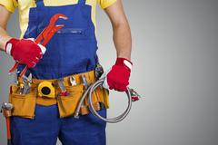plumber with tool belt isolated on gray with copy space - stock photo