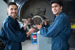 Mechanics examining car brake Stock Photos