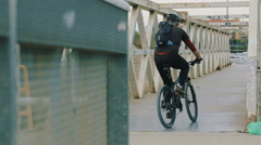 Сyclist riding a bicycle on a bridge. Stock Footage