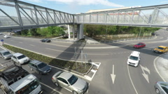 Vehicles Driven Through Traffic Circle Under Pedestrian Bridge Stock Footage