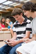 Teenage boys listening to music and playing a video game Kuvituskuvat