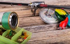 fishing tackles on background of dry stems - stock photo