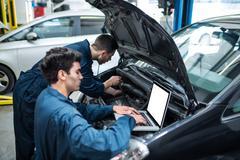 Mechanics examining car engine using laptop Kuvituskuvat