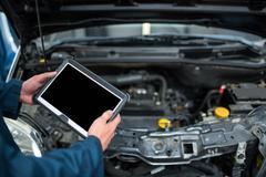 Mechanic holding diagnostic tool Stock Photos