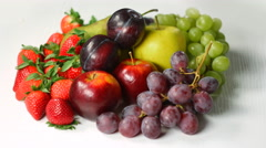 Fresh fruits of temperate zone rotating on a white table 4K. Stock Footage