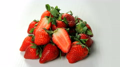 A heap of strawberries with leafs rotating on white table 4K. - stock footage