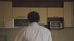 Drunk man comes home drunk and looking for a drink in the kitchen. Stock Footage