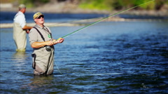 Fisherman using rod and reel casting line in freshwater river - stock footage