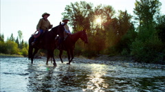Cowboys with horses in forest river wilderness area Canada Stock Footage
