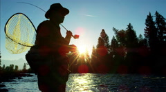 Sunrise silhouette of man with keep net freshwater fishing in river Canada - stock footage