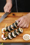 Slicing sushi with crab, salmon, cucumber Stock Photos