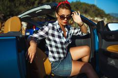 Beautiful pin up woman sitting in cabriolet, enjoying trip on luxury modern c Stock Photos