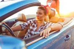 Two young happy girls driving a cabriolet Stock Photos
