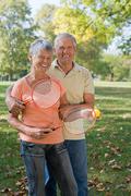 Senior couple playing badminton - stock photo