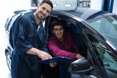 Happy mechanic and customer while holding quotation Stock Photos
