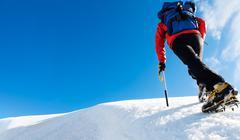 A climber reaches the top of a snowy mountain. Stock Photos