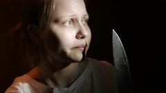 Teen girl with a big knife, horror movie dark scene, 4K UHD - stock footage