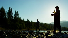 Sunrise silhouette rod and reel fishermen casting line in freshwater river USA - stock footage