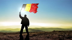 Successful silhouette man winner waving Belgium flag on top of the mountain p Stock Footage