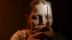 Addicted junkie teen girl with a syringe sitting and thinking about something - stock footage