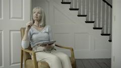 Senior Adult Female reading on digital tablet - stock footage