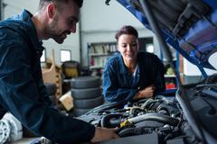 Team of mechanics examining car engine Stock Photos
