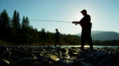 Skilled hobby fisherman in silhouette casting line for freshwater fishing - stock footage