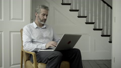 Mature Adult Male working from home on laptop Stock Footage