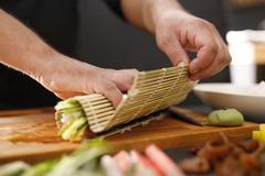 How to prepare sushi. Twisting sushi rolls on a bamboo mat Stock Photos