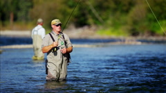 American fisherman wading in Wilderness river fly fishing USA Stock Footage