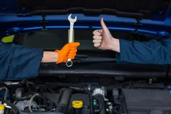 Mechanics holding spanner and showing thumbs up Stock Photos