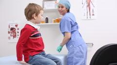 Nurse giving young boy lollipop - stock footage