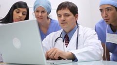 Medical personnel looking at laptop computer - stock footage