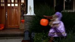 Children in Halloween costumes trick or treating Stock Footage