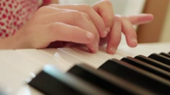 Little girl in red dress plays piano Stock Footage