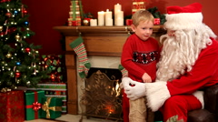 Santa Claus giving gift to young boy Stock Footage