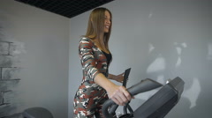 Woman training on a cross trainer in the gym Stock Footage