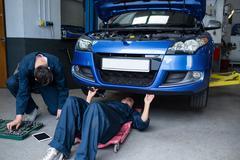 Mechanics repairing a car Stock Photos