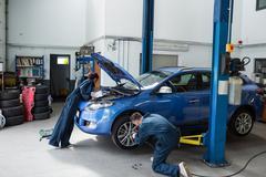 Mechanics examining a car engine and fixing wheel Stock Photos