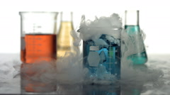 Science beaker bubbling and smoking, slow motion - stock footage
