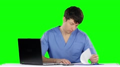 Doctor uses a computer and talking on the phone. Green screen - stock footage