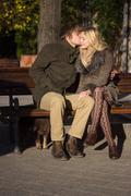 Young intimate romantic couple sitting on wood bench Stock Photos