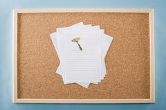 Paper and darts on a noticeboard Stock Photos