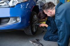 Mechanics fixing a car wheel Stock Photos