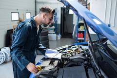 Mechanic checking the oil level in a car engine Stock Photos