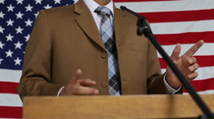 Man speaking at podium, flag background - stock footage