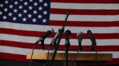 Microphone podium against american flag - stock footage