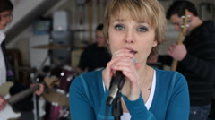 Woman sings with band in garage Stock Footage